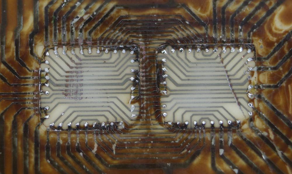 This closeup of the substrate shows how the two dies are wired together, mostly in parallel, by wiring underneath the dies.