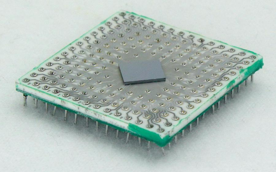 The integrated circuit with the metal lid removed, showing the silicon die on the ceramic substrate.