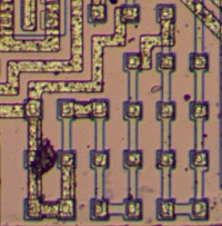 The LM308 op amp contains several resistors with resistance than can be modified by changing the metal layer. This image shows one resistor with about 20 segments. A few of the segments are shorted out with metal, reducing the resistance.