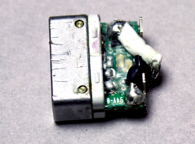 After removing more plastic, the circuit board inside a Magsafe connector is visible. The power cable is soldered onto the board.