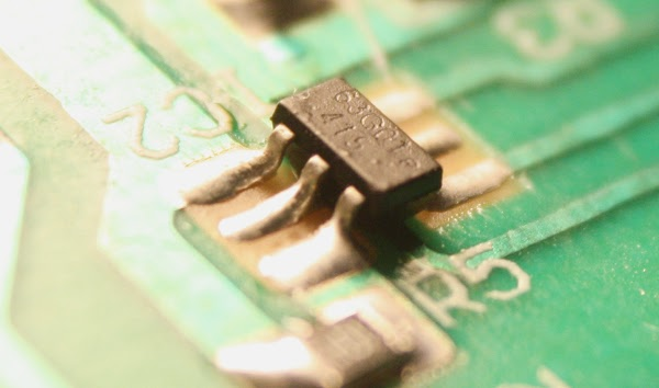 Closeup of the tiny control IC inside a counterfeit MagSafe 45W power supply.