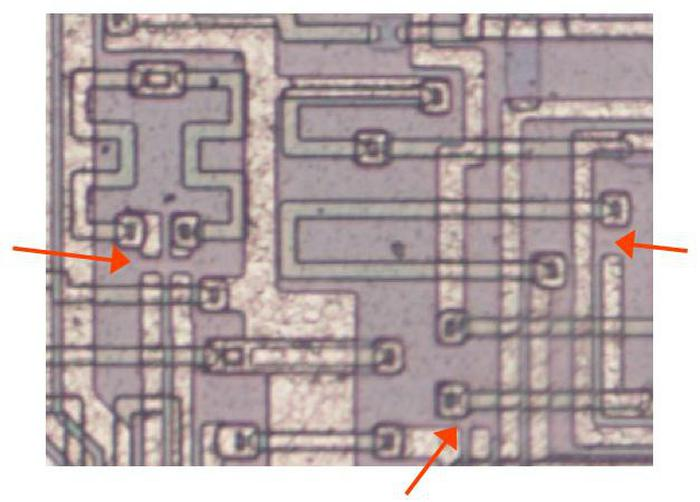 Closeup of the die with some broken connections indicated with arrows.
