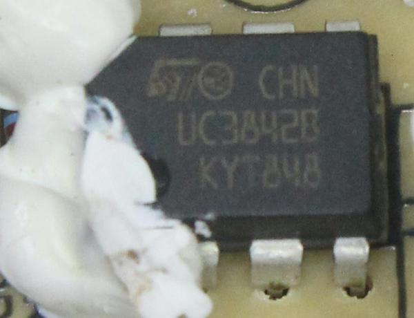 The UC3842 chip mounted on the power supply's circuit board. The white glob is silicone, which held many of the power supply components in place.