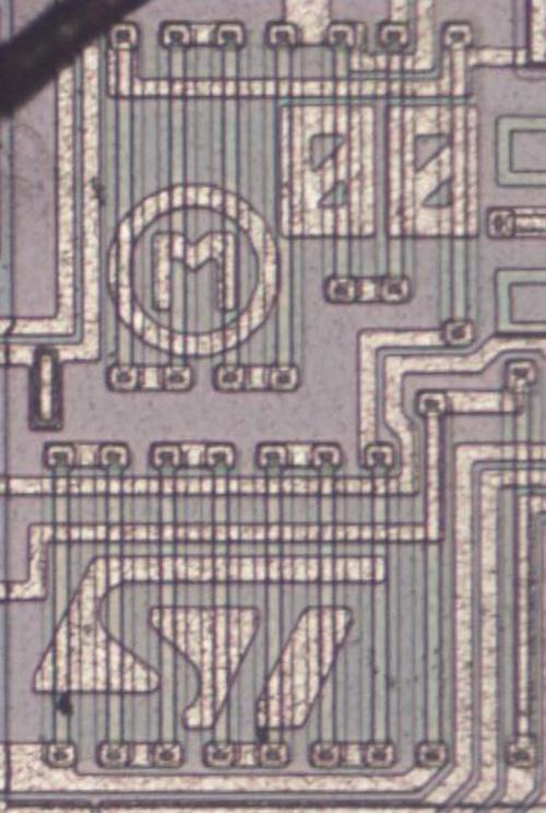 """This set of resistors forms voltage dividers to reduce the input voltage for the bandgap comparator. Note the mask date of """"00"""" as well as the ST Microelectronics logo at the bottom."""
